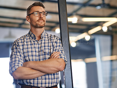 Buy stock photo Shot of an office worker looking thoughtful while leaning against a glass door