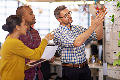 Buy stock photo Shot of a group of coworkers brainstorming at a whiteboard