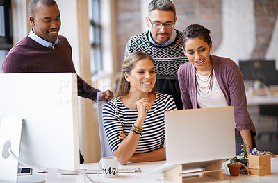 Buy stock photo Shot of a group of designers working together at a computer