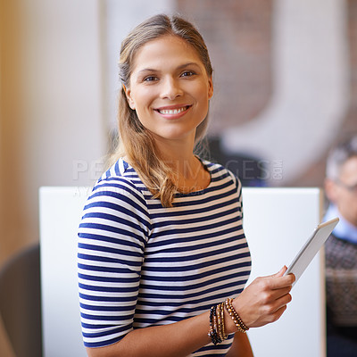 Buy stock photo Shot of a young businesswoman using a digital tablet in the office