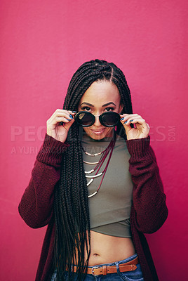 Buy stock photo Portrait of a young woman with braids posing against a pink background