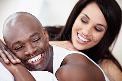 Buy stock photo Shot of a young couple laughing while lying in bed together