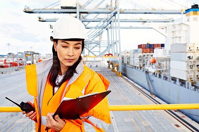 Buy stock photo Shot of a woman in workwear holding a clipboard and walkie talkie while standing on a large commercial dock