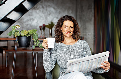 Buy stock photo Portrait of a mature woman sitting in her living room drinking a coffee and reading the newspaper