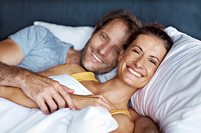Buy stock photo Portrait of an affectionate mature couple lying in bed together