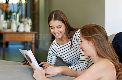 Buy stock photo Shot of two friends reading a magazine together at home