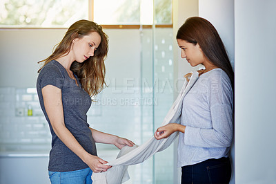 Buy stock photo Shot of a young woman helping her friend choose a dress to wear while standing in a bathroom