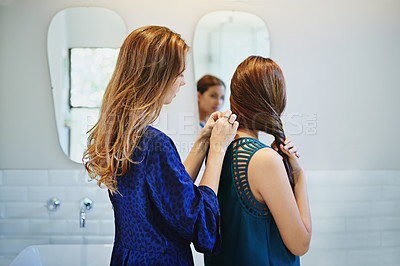 Buy stock photo Shot of a young woman helping her friend put on a necklace