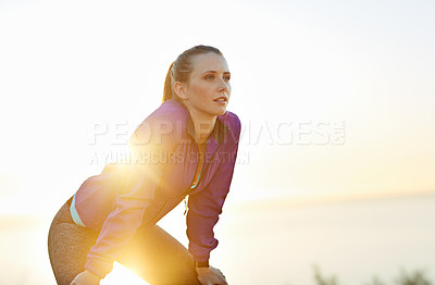 Buy stock photo Shot of a young woman taking a breather while out for a run