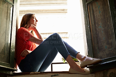 Buy stock photo Low angle shot of a young woman sitting on a window sill looking outside
