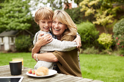 Buy stock photo Portrait of a grandmother and her grandson hugging while sitting at a table in her yard