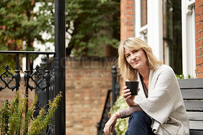 Buy stock photo Shot of a mature woman sitting on her front porch drinking a cup of coffee