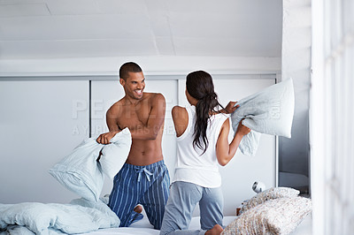 Buy stock photo Shot of a young couple kneeling on their bed having a pillow fight