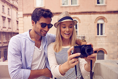 Buy stock photo Shot of a young couple taking photos while exploring a foreign city