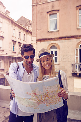 Buy stock photo Shot of a young couple looking at a map while exploring a foreign city