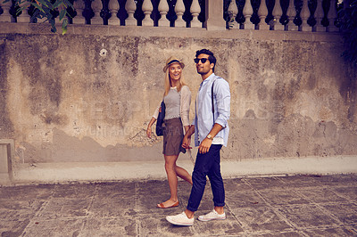 Buy stock photo Shot of a young couple exploring a foreign city