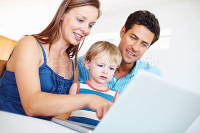 Buy stock photo Family of three using laptop with woman pointing at the screen