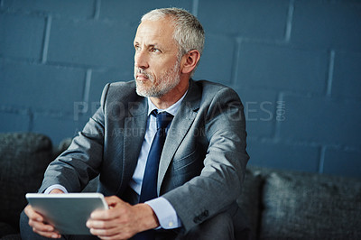 Buy stock photo Shot of a thoughtful businessman using a digital tablet
