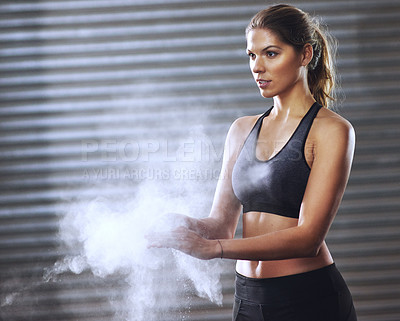 Buy stock photo Shot of a young woman coating her hands with sports chalk before a workout
