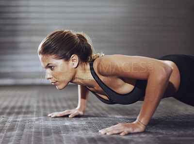 Buy stock photo Cropped shot of a young woman doing push-ups at the gym