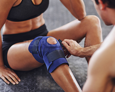 Buy stock photo Shot of a sportswoman being helped with a knee injury