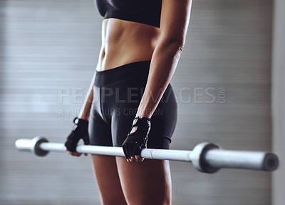 Buy stock photo Cropped shot of a woman training with weights at the gym