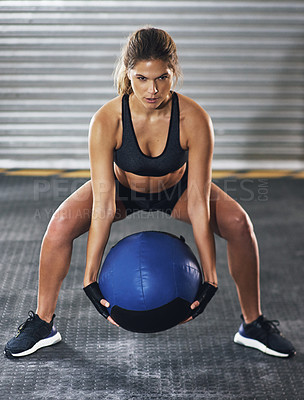 Buy stock photo Shot of a young woman working out with a medicine ball at the gym