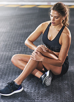 Buy stock photo Shot of a sportswoman with a knee injury