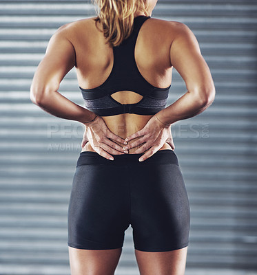 Buy stock photo Shot of a sportswoman with a lower back injury