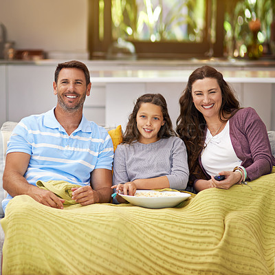 Buy stock photo Shot of a family sitting on their living room sofa watching a movie and eating popcorn