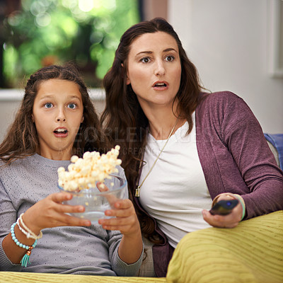 Buy stock photo Shot of a mother and daughter sitting on their living room sofa watching a movie and eating popcorn