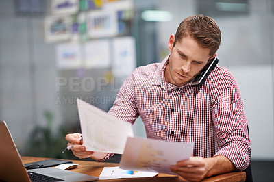 Buy stock photo Shot of a young businessman sitting at a desk talking on his phone while going through paperwork