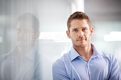 Buy stock photo Portrait of a young businessman leaning against a glass wall in an office