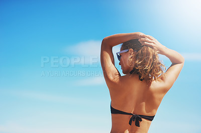 Buy stock photo Rearview shot of a young woman standing on the beach