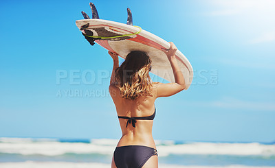 Buy stock photo Rearview shot of a young surfer holding her surfboard on her head at the beach