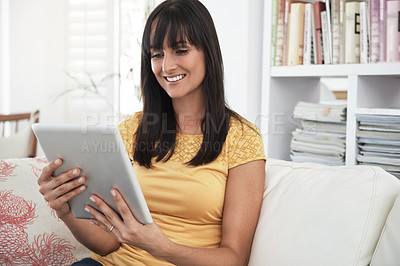 Buy stock photo Cropped shot of a woman using a digital tablet at home