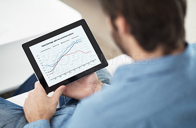 Buy stock photo Cropped shot of a man working on his digital tablet at home