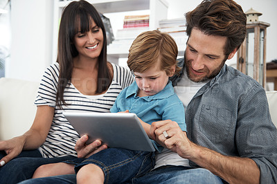 Buy stock photo Shot of a family of three using a digital tablet at home