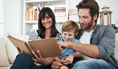 Buy stock photo Shot of a family looking through a photo album together