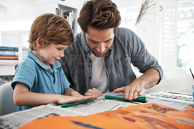 Buy stock photo Shot of a father and son doing arts and crafts at home