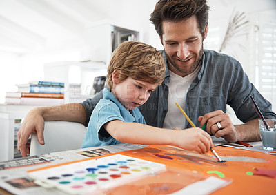 Buy stock photo Shot of a father sitting with his son while's he's working on an art project