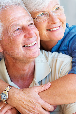 Buy stock photo Closeup of happy senior couple smiling and looking away with woman embracing man from behind