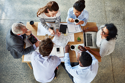Buy stock photo High angle shot of a group of coworkers sitting around a table in the boardroom