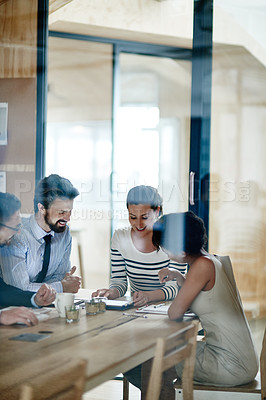 Buy stock photo Through glass shot of a group of colleagues working together in an office