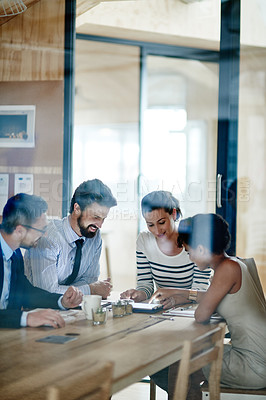 Buy stock photo Through the glass shot of a group of colleagues working together in an office