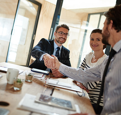 Buy stock photo Shot of two businesspeople shaking hands in an office while a colleague look on