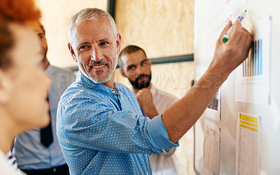 Buy stock photo Shot of a mature businessman explaining something to his colleagues on a whiteboard