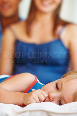 Buy stock photo Closeup of little kid lying on sofa with thumb in mouth and parents in background