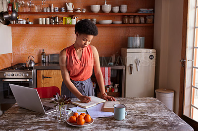 Buy stock photo Shot of a young woman writing in a diary while working in her kitchen