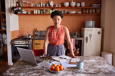 Buy stock photo Portrait of a young woman working on a laptop in her kitchen